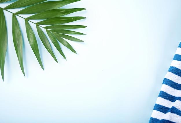 青の背景にストライプのビーチタオルと熱帯の葉。最小限の概念平らに置きます。 copyspace