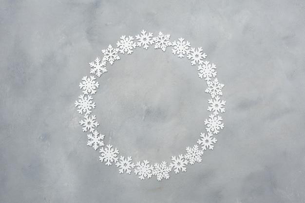Рамка из снежинок белого рождества круглая с copyspace на сером цвете