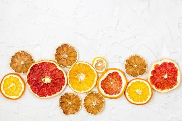 白い背景にさまざまな柑橘系の果物の乾燥スライスの境界線。オレンジレモングレープフルーツcopyspace