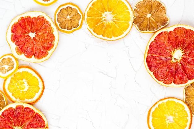 白い背景にさまざまな柑橘系の果物の乾燥スライスの境界線。 copyspaceとオレンジレモングレープフルーツ