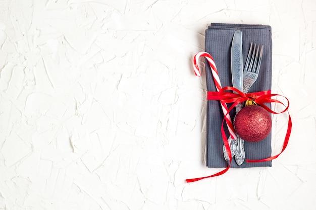 ナイフ、フォーク、赤いボール、キャンディケイン、copyspaceの白いテーブルの上のリボンとクリスマステーブルの場所の設定