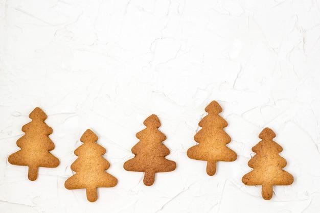 Copyspaceと白い表面にクリスマスの自家製ジンジャーブレッドクッキーの背景