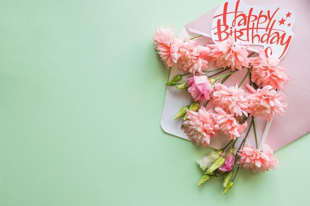 花の組成ピンクの菊のクリエイティブボーダー。封筒の菊。フラットレイアウト、上面図、copyspace。
