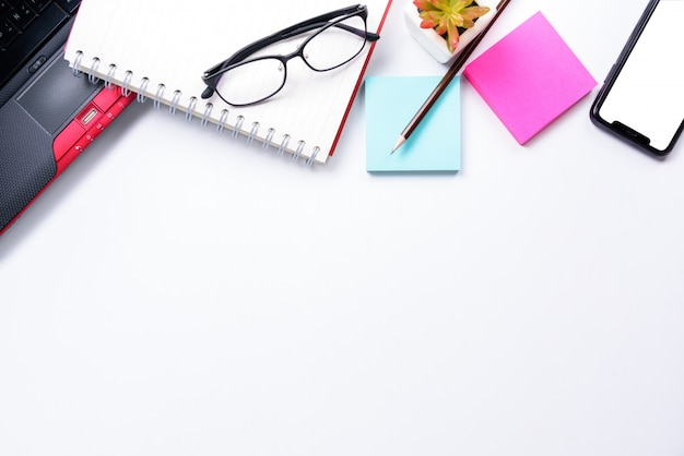 トップビューまたはフラットレイアウトスタイルのラップトップ、ペン、ノートブック、眼鏡、付箋、白いテーブル背景に携帯電話とワークスペースのcopyspace
