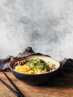 Холодный корейский суп кукси с овощами, яичницей, говядиной и лапшой в миске и палочками для еды. copyspace