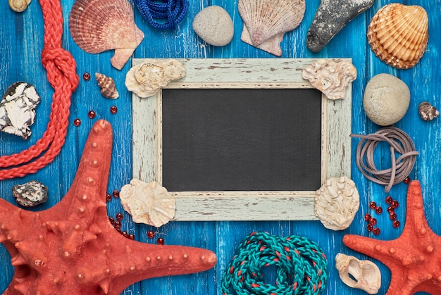 Пустой доске с морских раковин, камней, веревки и звезды рыбы на синем, деревянные, copyspace
