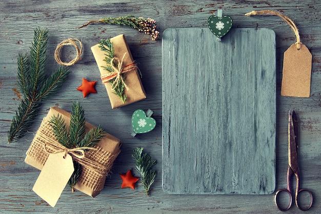 Подарки ручной работы на деревенском деревянном столе с рождественскими украшениями, copyspace
