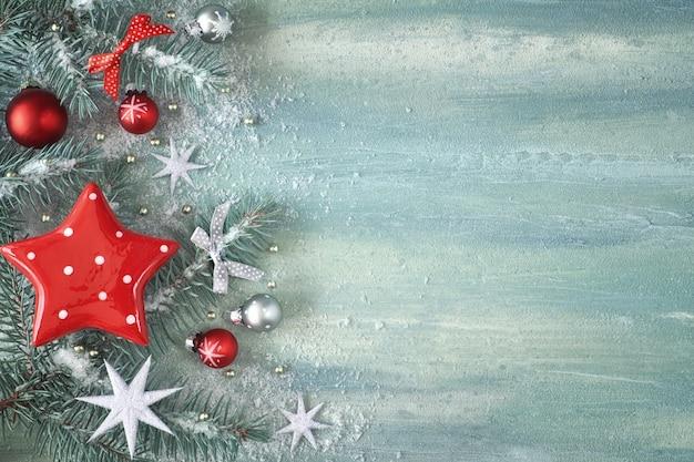 Рождество с еловыми ветками, светло-зелеными безделушками и серебряными звездами на светлом абстрактном фоне, текст copyspace