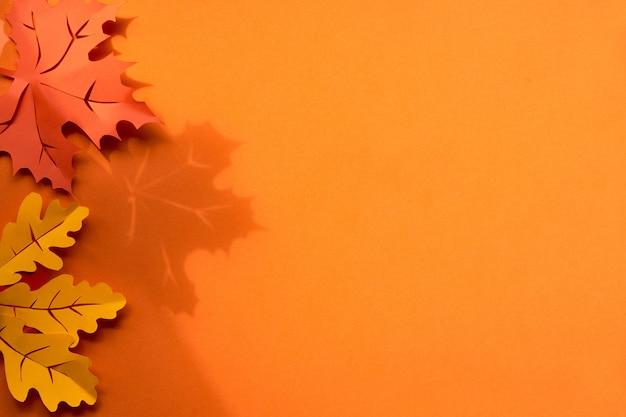 影とcopyspaceで用紙の背景にメープルとオークの葉。創造的な手作りのペーパークラフト、フラットレイアウト。トーンの秋の背景。