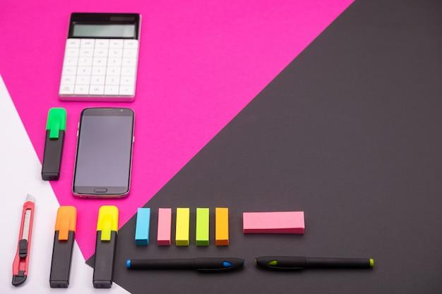 Картина современного рабочего места с калькулятором, маркерами, канцелярскими товарами и смартфоном с copyspace на розовый и черный