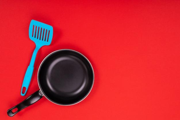 赤の背景にcopyspaceで分離されたキッチンで調理器具