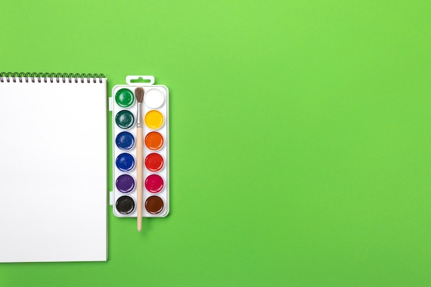 水彩絵の具と緑の背景にcopyspaceでペイントするためのキャンバスとブラシ