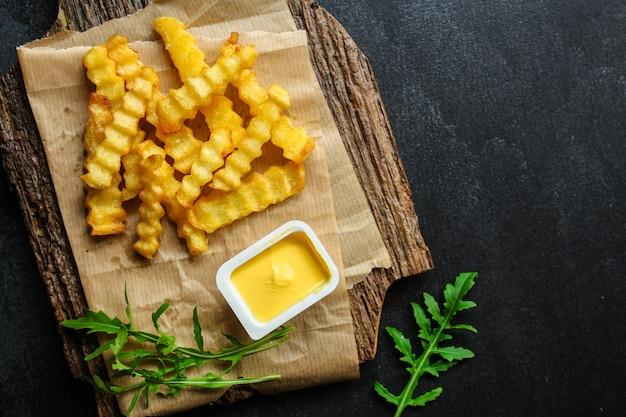 Картофель фри и соус вкусные закуски, фаст фуд, картофель фри меню. еда copyspace. вид сверху