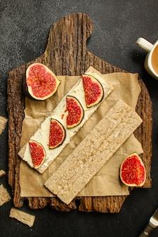 健康食品、サンドイッチ、ぱりっとしたパン、イチジク、コーヒーの朝食またはスナック、クリームチーズ、バター、ヨーグルトメニュー。食物 。 copyspace。上面図