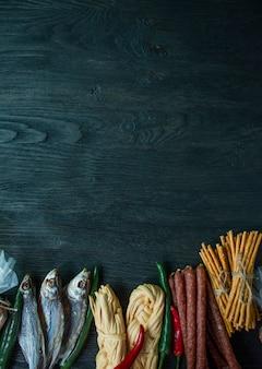 Закуски к пиву, орехам и крекерам. пивные закуски упакованы в целлофан. темный деревянный фон. copyspace