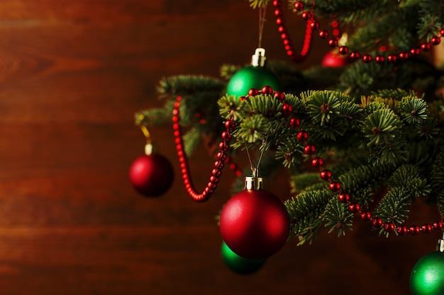 Рождественская елка, наряженные шарики, стоит на деревянном столе. copyspace.