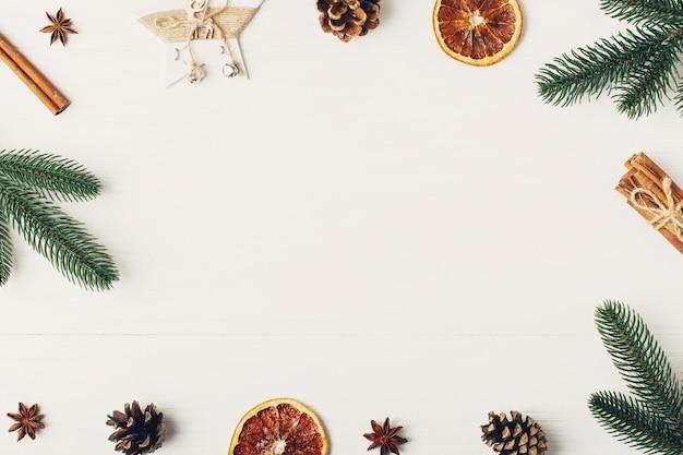 Декоративная рамка, рождественские атрибуты на белом деревянном столе. место для текста, бланк для открытки. copyspace.