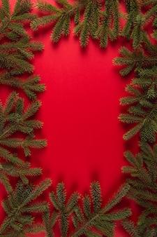 赤、クリスマス、グリーティングカードcopyspaceのフレームの形でクリスマスツリーの枝。