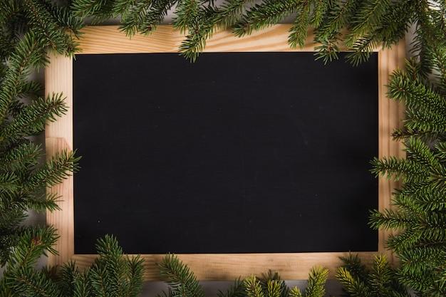 クリスマスツリーの枝と黒の木板フレーム、クリスマス、グリーティングカード。 copyspace。