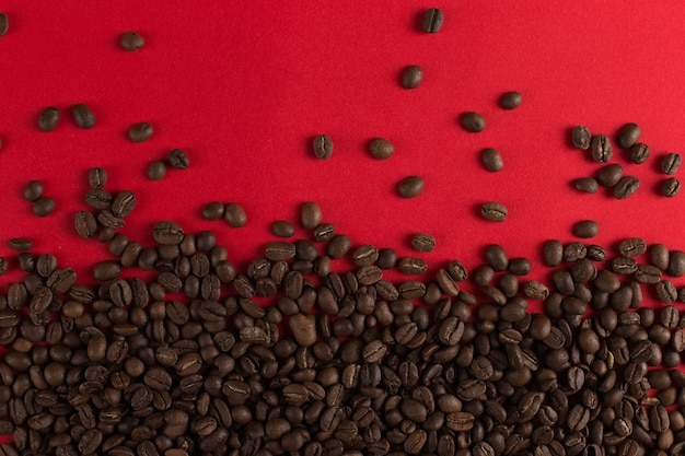 Кофейные зерна разбросаны на красной бумаге крупным планом, коммерческие copyspace.