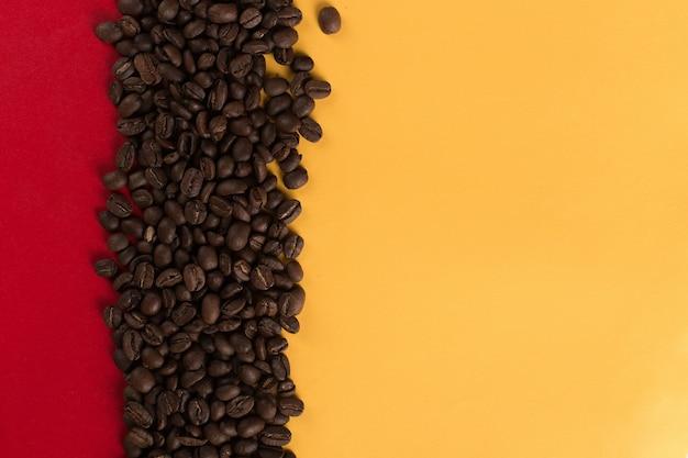 Кофейные зерна разбросаны на красный и желтый бумаги крупным планом, коммерческие copyspace.