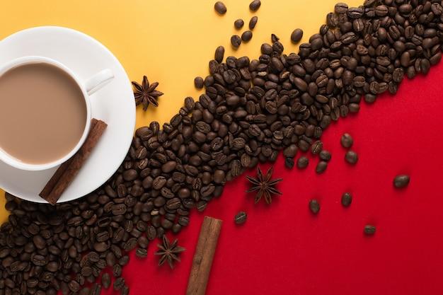 Кофейные зерна разбросаны по красной и желтой бумаге и белой чашке, корице, анису, коммерческому copyspace.
