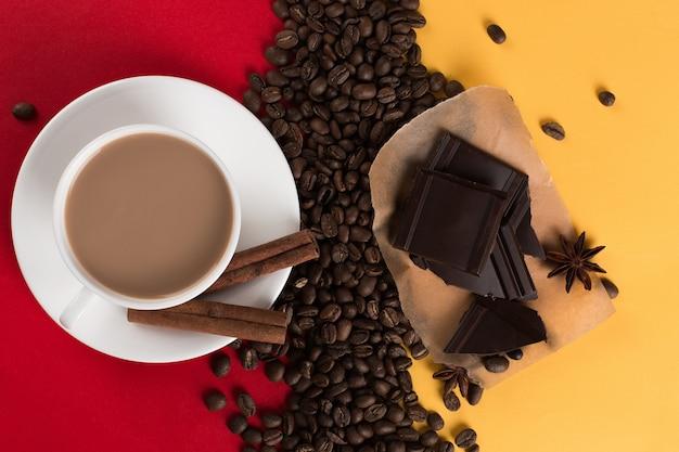 Кофейные зерна разбросаны по красной и желтой бумаге и белой чашке, корице, звездчатому анису, шоколаду, коммерческому copyspace.