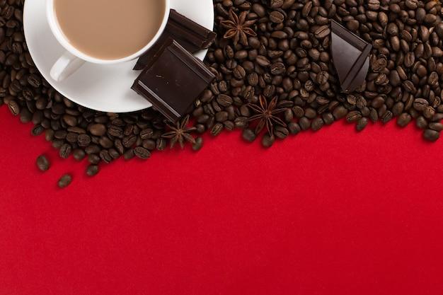 Кофейные зерна разбросаны на красной бумаге и белой чашке, шоколад, коммерческие copyspace.