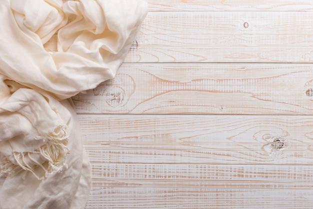 木製のテーブルに白いスカーフ。秋の背景、copyspace。