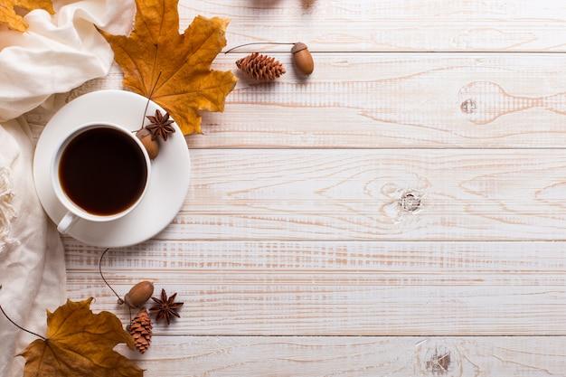 木製のテーブルに白いスカーフ、コーヒーと乾燥した黄色の葉。秋の気分、copyspace。