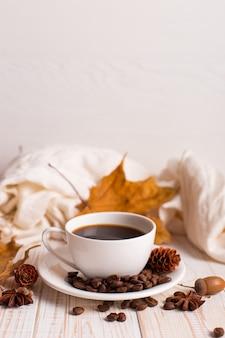 白いスカーフ、散らばったコーヒー豆とコーヒーカップ、木製のテーブルに黄色の葉を乾燥させます。秋の気分、copyspace。