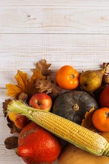 さまざまな野菜のカボチャ、リンゴ、梨、ナッツ、トウモロコシ、トマト、白い木製の背景に黄色の葉を乾燥させます。秋の収穫、copyspace。