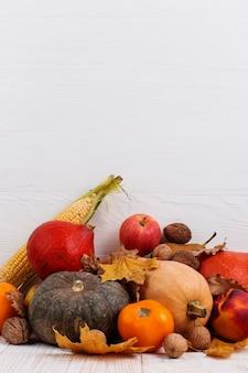 さまざまな野菜、カボチャ、リンゴ、梨、ナッツ、トウモロコシ、トマト、白い木製の背景に乾燥した葉。秋の収穫、copyspace。