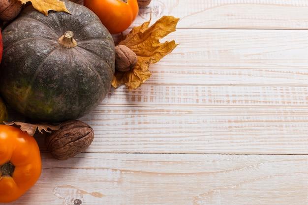 さまざまな野菜、カボチャ、リンゴ、梨、ナッツ、トマト、白い木製の背景に乾燥した葉。秋の気分、copyspace。収穫。