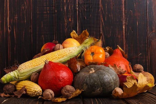 Различные овощи, тыквы, яблоки, груши, орехи, помидоры, кукуруза, сухие желтые листья на деревянном фоне. осеннее настроение, copyspace. уборка урожая .