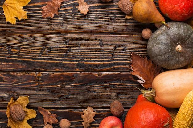 さまざまな野菜、カボチャ、リンゴ、梨、ナッツ、トマト、トウモロコシ、木製の背景に黄色の乾燥葉。秋の気分、copyspace。収穫。