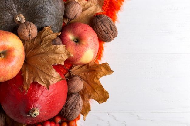 明るいオレンジ色の暖かいショール、カボチャ、果実、リンゴ、ナッツ、白い背景、秋の気分、copyspaceの乾燥した黄色の葉。収穫。