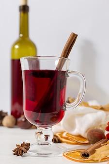 Чашка глинтвейна с пряностями, бутылка, шарф, специи, сухие листья и апельсины на столе. осеннее настроение, способ согреться в холоде, copyspace.