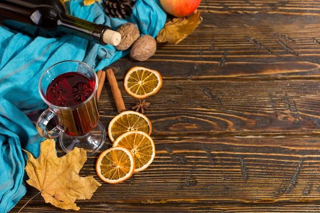 Чашка глинтвейна с пряностями, бутылка, шарф, сухие листья и апельсины на деревянном столе. осеннее настроение, способ согреться в холоде, copyspace.