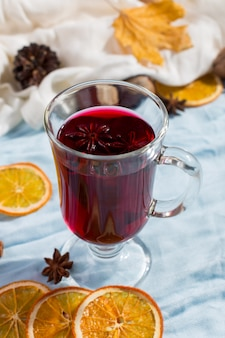 Чашка глинтвейна с пряностями, сухие листья и апельсины на столе. осеннее настроение, способ согреться в холоде, copyspace, утренний свет.