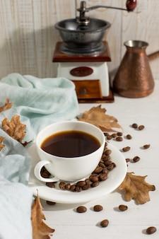 乾燥した黄色の葉、青いスカーフ、コーヒー粒、白いテーブルの上のカップ、朝の開始日。秋の気分背景、copyspace。