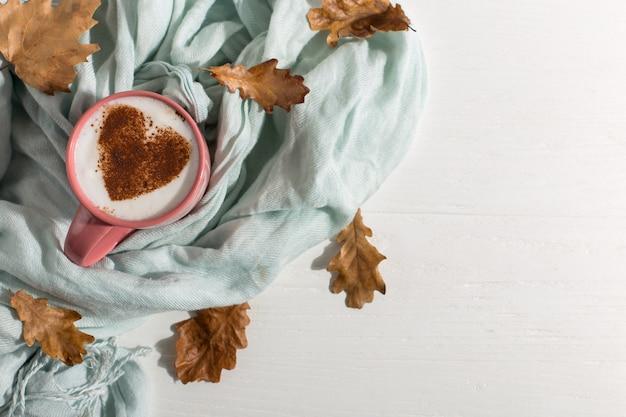 乾燥した黄色の葉、青いスカーフ、テーブルにハート柄のコーヒー、おはようが最高の開始日です。秋の気分背景、copyspace。