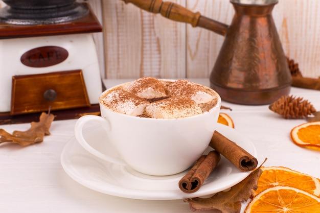 マシュマロとココア、葉、乾燥オレンジ、スパイス、白い背景の上のコーヒーカップ。おいしい熱い秋の飲み物、朝の気分。 copyspace。