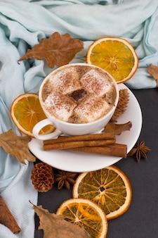 Чашка кофе с маршмеллоу, какао, шарф, листья, сушеные апельсины, специи, на сером фоне. вкусный горячий осенний напиток, утреннее настроение. copyspace.