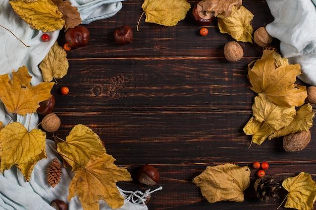 木製のテーブルにスカーフ、栗、ナッツ、乾燥葉。秋の背景、copyspace。