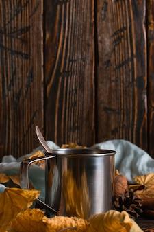 ブラックコーヒー、スパイス、スカーフの背景に鉄のマグカップ、木製のテーブルに乾燥葉。秋の気分、温かい飲み物。 copyspace。