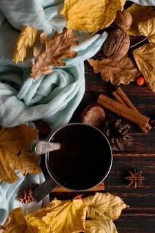 Железная кружка с черным кофе, специями, на фоне шарфа, сухими листьями на деревянном столе. осеннее настроение, согревающий напиток. copyspace.