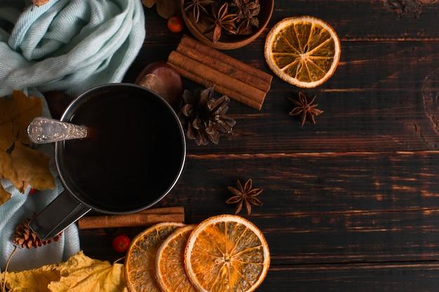 ブラックコーヒー、スパイス、乾燥オレンジ、スカーフの背景に鉄のマグカップ、木製のテーブルに乾燥した葉。秋の気分、温かい飲み物。 copyspace。