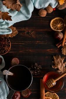 ブラックコーヒー、蜂蜜、スパイス、スカーフの背景に鉄のマグカップ、木製のテーブルに乾燥葉。秋の気分、温かい飲み物。 copyspace。