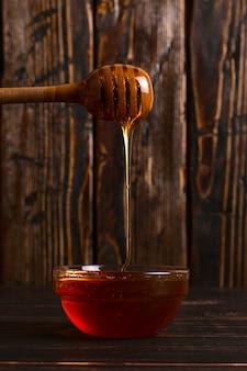 ハチミツは棒から瓶に流れ込みます。素朴な甘い写真、木製の背景、copyspace。